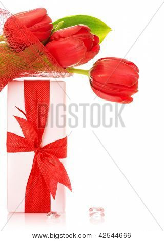 Picture of romantic holiday still life, red tulips bouquet with present isolated on white background, festive postcard, happy mothers day, gift for birthday, spring time, love concept