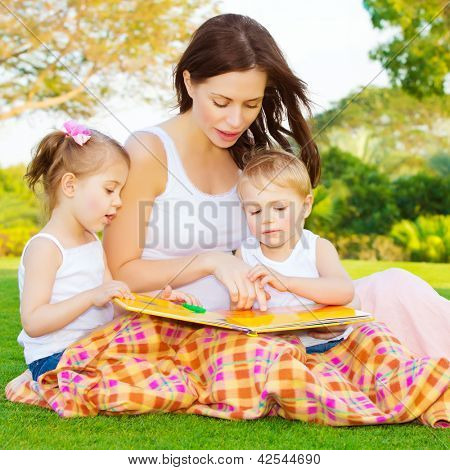 Image of cute young female with two little children read book outdoors, brother and sister with mother learning in the park in spring time, preschool education, day care, happy family concept