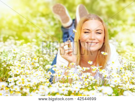 Photo of cute blond young lady enjoy beautiful spring nature, closeup portrait of pretty female lying down on chamomile field and holding one flower in hand, sunny day, happy woman, vacation concept