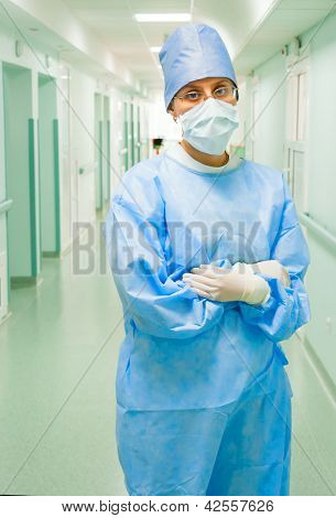 Young female surgeon in long clinic's corridor