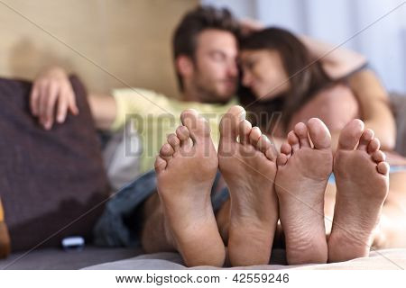 Young loving couple lying on sofa at home, relaxing in the afternoon. Focus on feet.