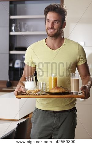 Handsome young man walking with breakfast tray in the morning.