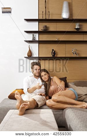 Young attractive couple sitting on sofa at home, watching tv.