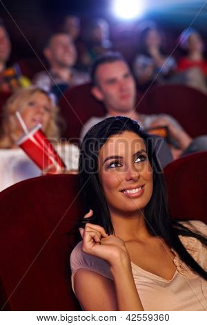 Beautiful young girl sitting in cinema, playing with hair, smiling.