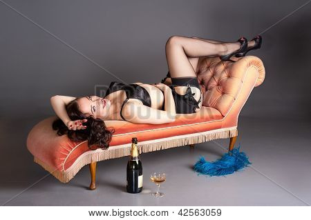 Retro pinup relaxes on chaise with champagne