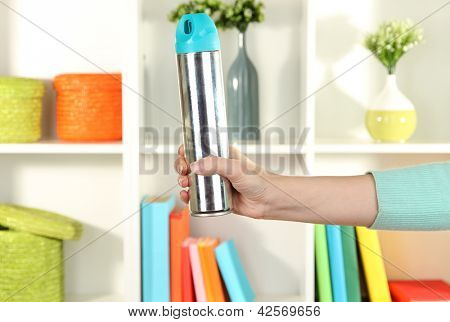 Sprayed air freshener in hand on white shelves background