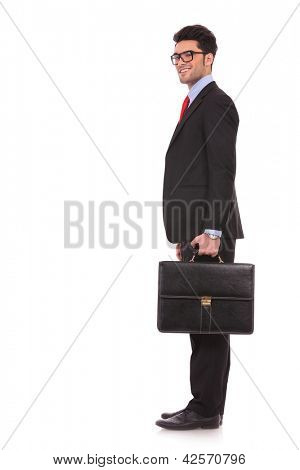 side view full length picture of a young business man  standing with his suitcase in his hand and turning his look at the camera with a smile on his face on white background