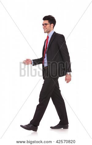 side view full length picture of a young business man walking and looking away from the camera on white background