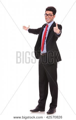 full length picture of a young business man presenting something in the back and showing thumbs up sign while smiling to the camera on white background