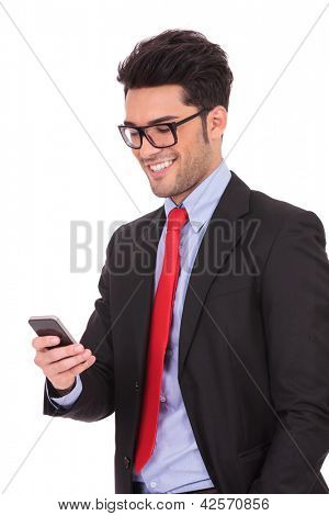 closeup portrait of a young business man standing with a hand in his pocket and texting on his phone, on a white background
