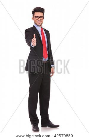 full length picture of a young business man putting his hand out to make a deal with you with a smile on his face, on white background