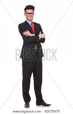 full length picture of a young business man standing with his hands folded and smiling to the camera on white background