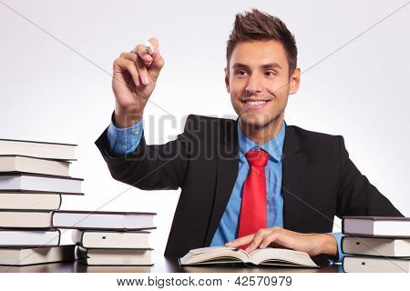 young business man sitting at his desk full of books and writing something with chalk on an imaginary screen