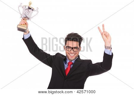 young business man holding up a trophy and showing victory sign with the other hand, while smiling to the camera
