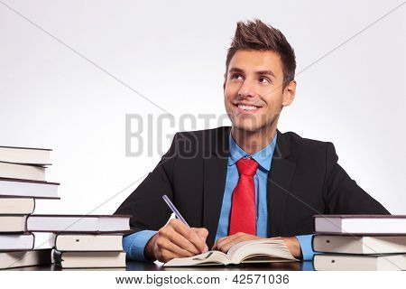 young business man at a desk full of books, thinking while witing with a smile on his face