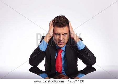 junger Geschäftsmann sitzt an seinem Schreibtisch und suchen verzweifelt Weg von der Kamera mit einem verrückten Blick auf