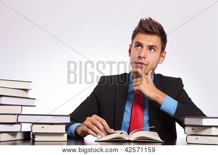 young business man sitting at the desk and reading with a contemplative look on his face