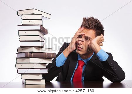young business man slaping himself while seeing the stack of books he has to read