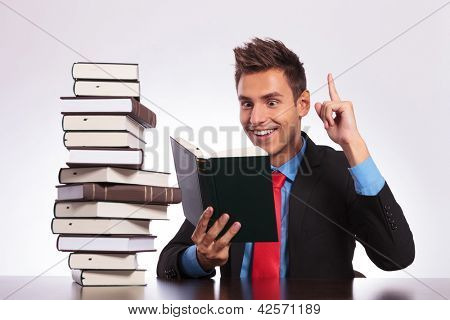 young business man having an idea while reading a book at his desk