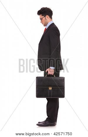 side view full length picture of a young business man standing with his suitcase in his hand and looking down, in front of him on white background