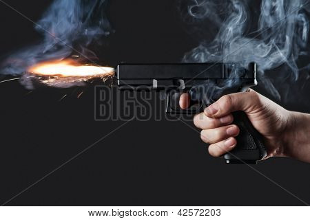 shot from a handgun with fire and smoke