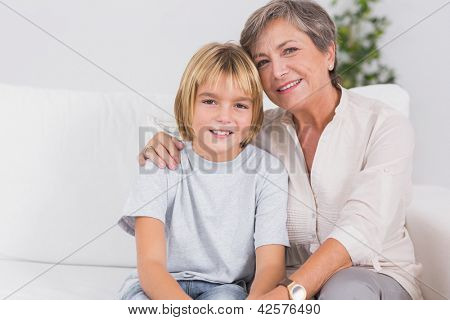 Portrait of a little boy and his grandmother smiling in sitting room