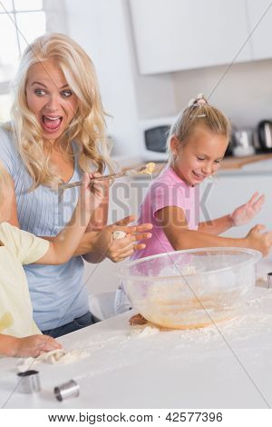 Mother making a face while her children take care of the dough to eggs