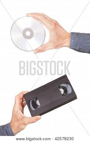 Cintas de video y unidad de Cd en su mano. Sobre un fondo blanco.