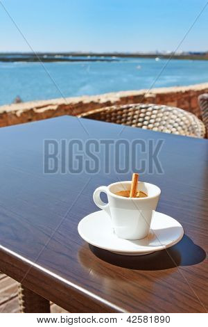 A Cup Of Coffee With A Stick Canela On The Table Outside.