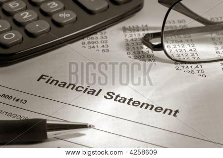 Estados financieros de corretaje con pluma y gafas