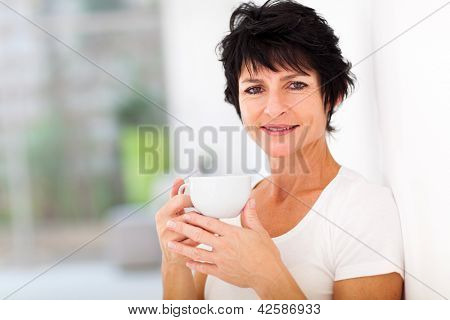 attractive mid age woman enjoying coffee at home