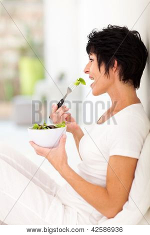 beautiful middle aged woman eating salad at home