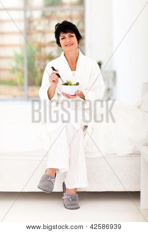 pretty middle aged woman holding bowl of salad sitting on bed