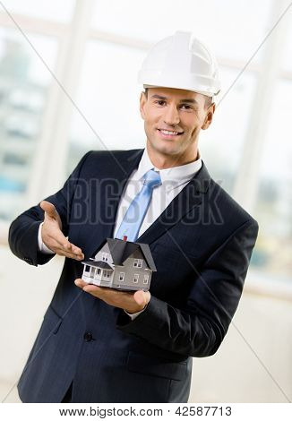 Engineer in white headpiece pointing at small model house. Concept of real estate