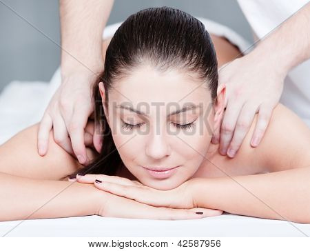 Woman receives shoulders massage at spa