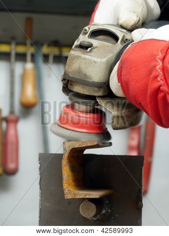 Closeup of machinist worker hands brushing a metal piece using wire brush on angle grinder