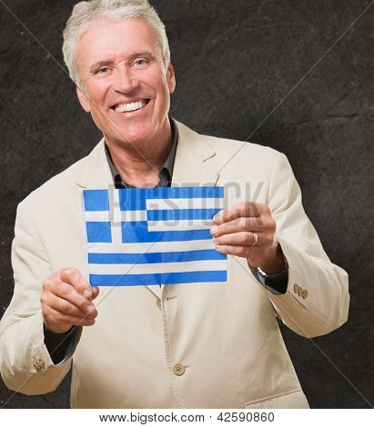 Businessman Holding Greece Flag against a grunge background