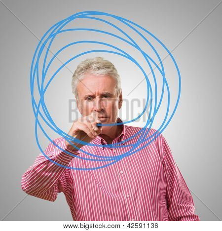 Mature Man Scribbling On Glass Over Gray Background