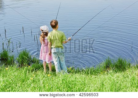 Boy in green t-shirt and his sister in pink dress fish in pond