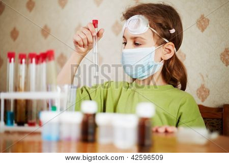 Girl in green t-shirt in respirator attentively looks at test tube with specimen in her hand