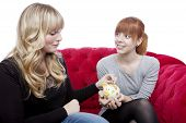 Young Beautiful Blond And Red Haired Girls Save Money In Pig On Red Sofa In Front Of White Backgroun