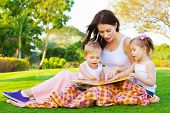 stock photo of mother baby nature  - Photo of young brunette woman teaching two sweet kids - JPG