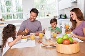 stock photo of fruit bowl  - Family eating healthy breakfast in kitchen - JPG