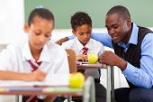 stock photo of schoolboys  - elementary school teacher helping student in classroom - JPG
