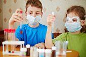 Постер, плакат: Мальчик и девочка сидеть за столом с химических реагентов и посмотрите на пробирки в их руках