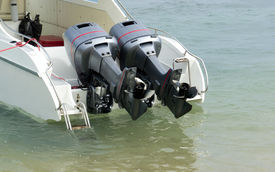 stock photo of outboard engine  - Two speed engines are lifted out of the water - JPG
