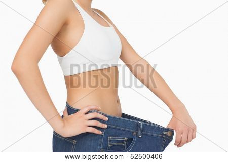 Mid section of slim young woman wearing too big jeans on white background