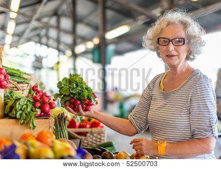 senior woman choosing vegetable at the market
