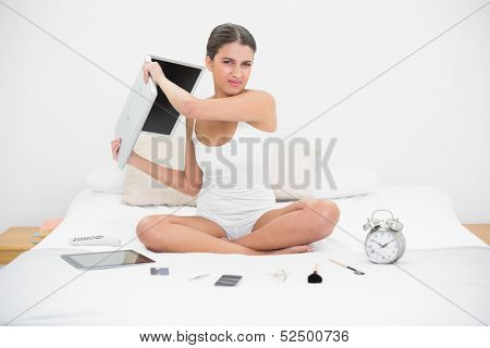 Furious young brown haired model in white pajamas throwing her laptop in bright bedroom