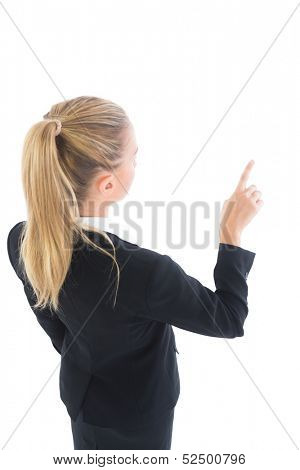 Attractive pony tailed business woman pointing on white background